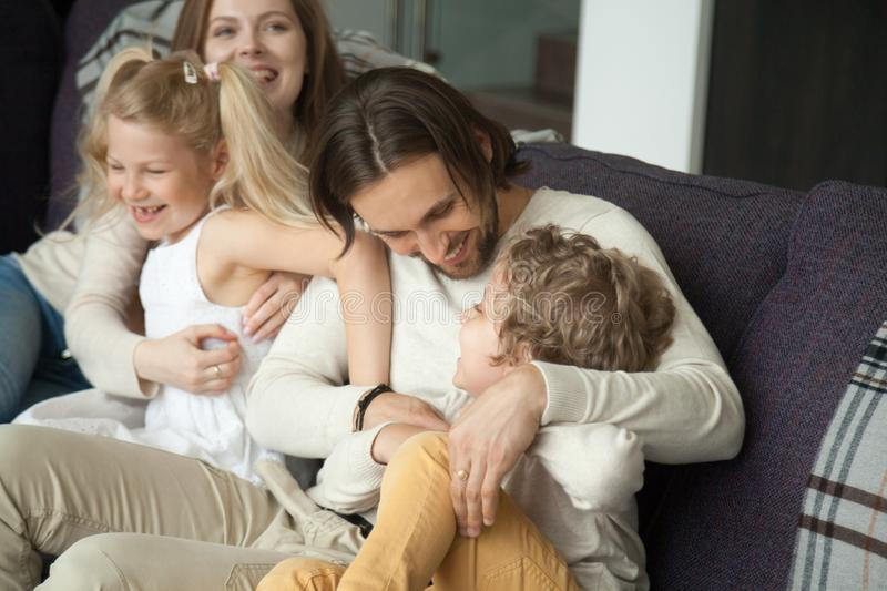 Happy parents and children laughing having fun tickling on sofa. Cheerful mom and dad embracing kids playing with son and daughter on couch, funny weekend stock photography