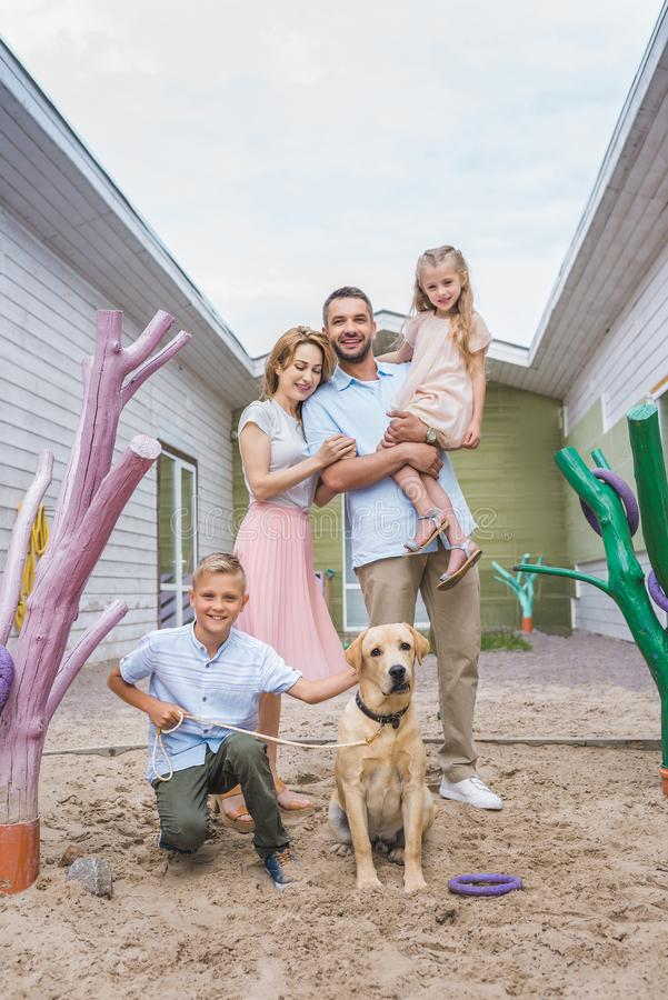 happy parents and children standing with adopted labrador dog royalty free stock photo