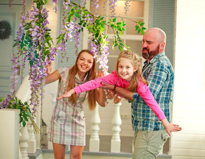 Happy parents with daughter have fun playing holding child on his hands, in courtyard summer family home royalty free stock photography