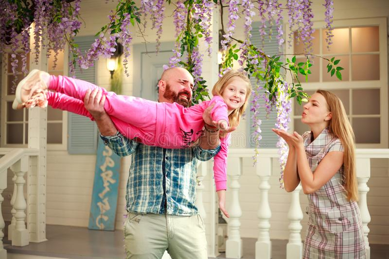 Happy parents with daughter have fun playing holding child on his hands, in courtyard summer family home stock photography