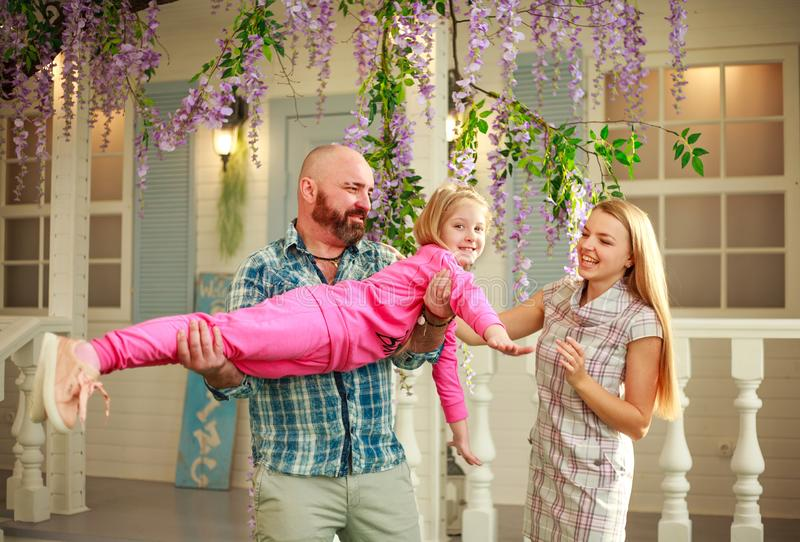 Happy parents with daughter have fun playing holding child on his hands, in courtyard summer family home royalty free stock image