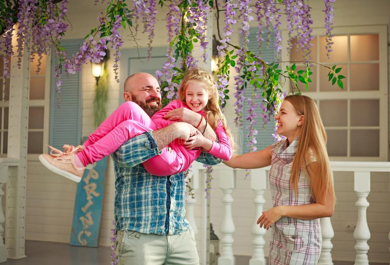 Happy parents with daughter have fun playing holding child on his hands, in courtyard summer family home stock photo