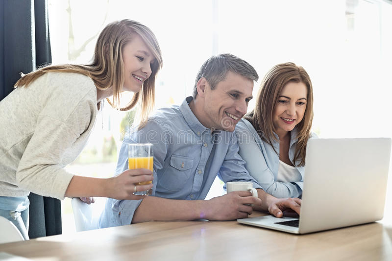 Happy parents with daughter using laptop at home royalty free stock photo