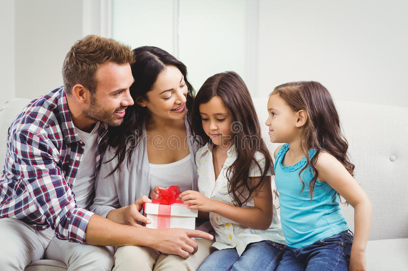 Happy parents with daughters holding gift. At home stock images