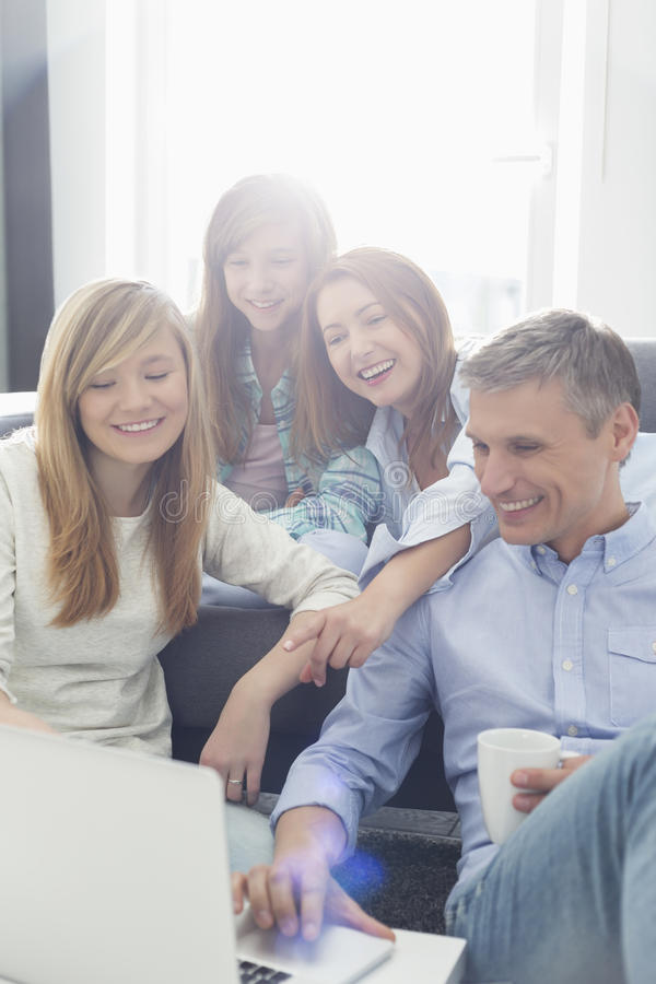 Happy parents with daughters using laptop in living room royalty free stock photos