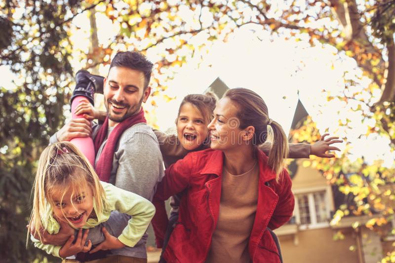 Happy parents have play with daughters. On the move. Young parents royalty free stock photo