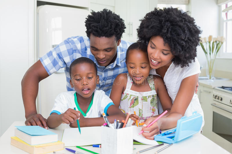 Happy parents helping children with homework stock photography