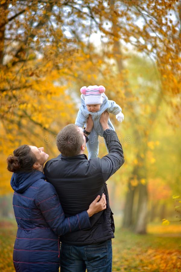Happy parents are holding their beloved baby in the arms stock images