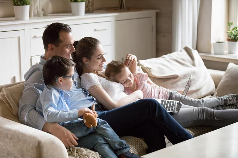 Parents cuddle with children watching kid video at laptop stock image