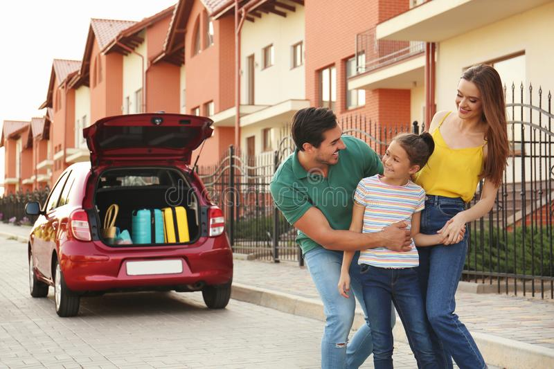 Happy parents hugging their daughter near family car royalty free stock images