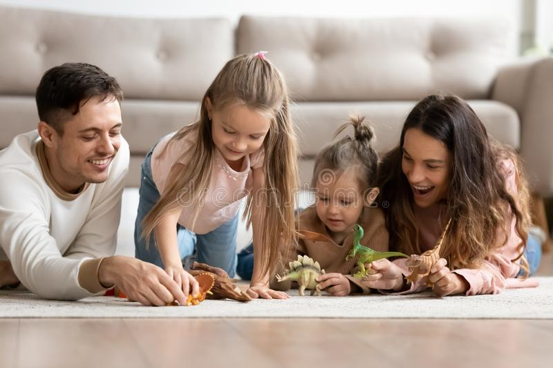 Happy parents and kids daughters playing with dinosaurs on floor. Happy family young parents and cute small kids daughters playing with dinosaurs on floor carpet royalty free stock photography