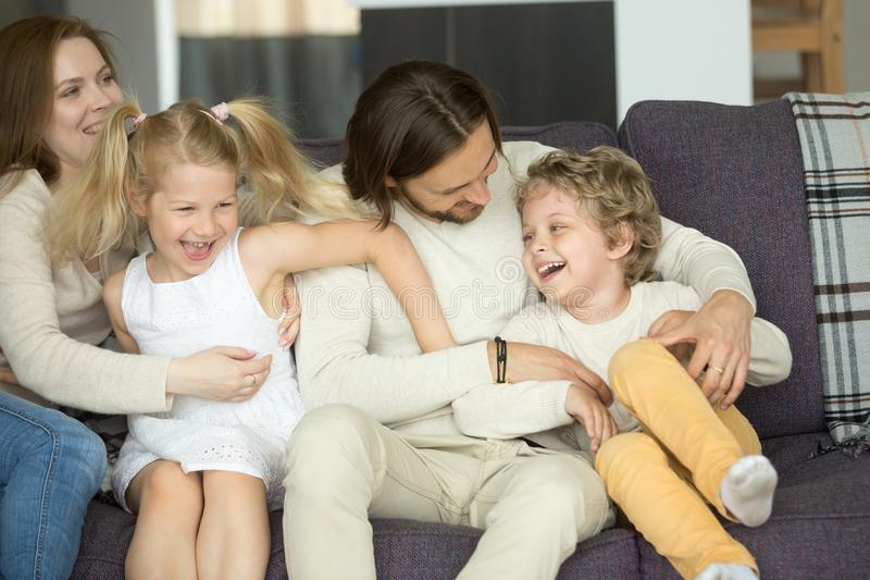 Happy parents and kids laughing having fun sitting on sofa. Young married couple embracing preschool smiling son and daughter on couch, cozy warm loving caring stock image