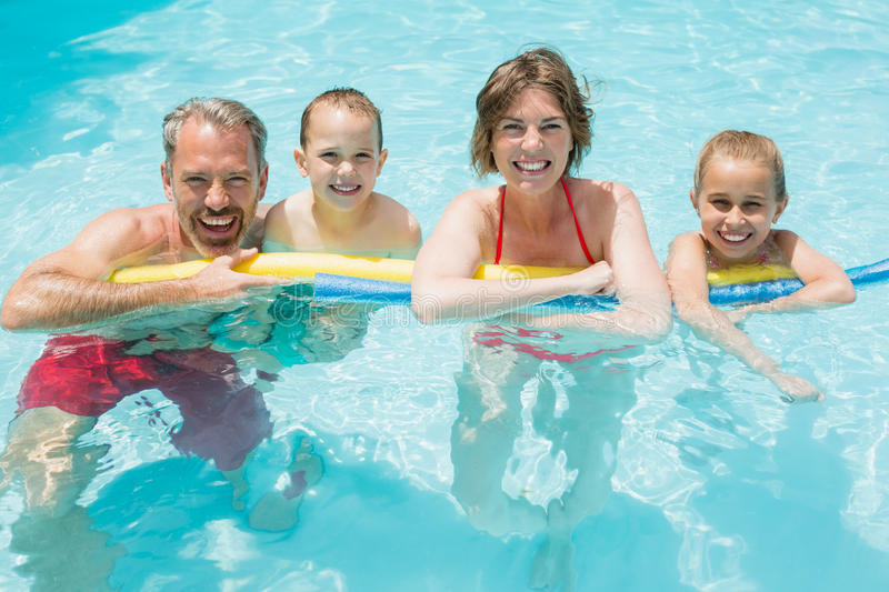 Happy parents and kids in pool stock photo
