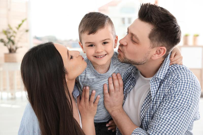 Happy parents kissing their son. Family time stock photos