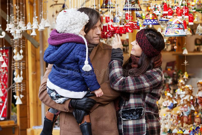 Happy parents and little child watching handmade bell at traditional  European Xmas street market. Family with kid shopping for royalty free stock images