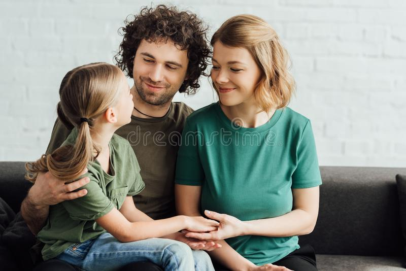 happy parents looking at cute little daughter while sitting on couch royalty free stock photo