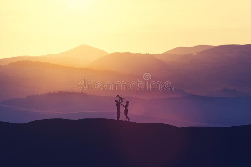 Happy parents playing with the baby on the hills. stock illustration