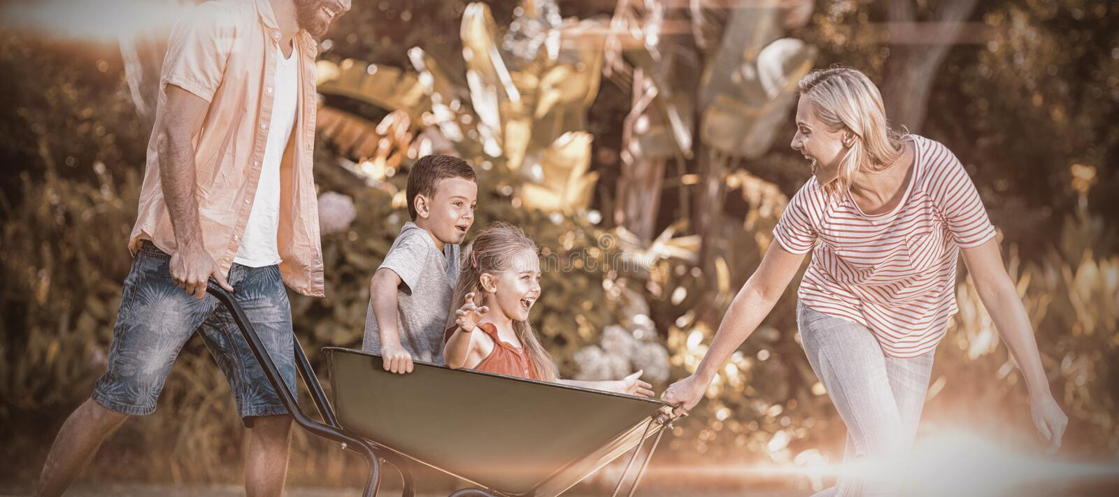 Parents pushing children sitting in wheelbarrow at yard stock images
