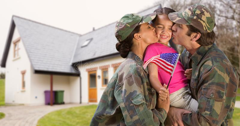 Happy parents in soldiers uniform kissing their daughter stock image