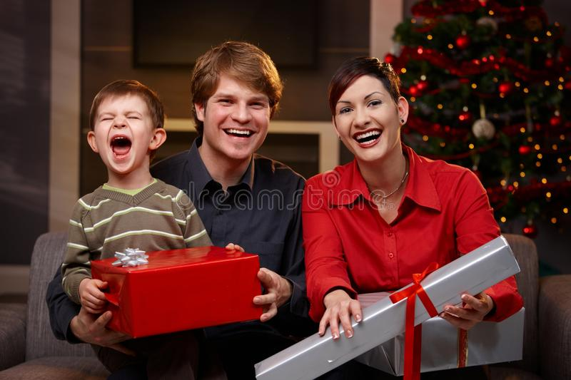 Happy parents and son with christmas gifts. Happy parents and son sitting at couch, holding christmas gifts, laughing royalty free stock photos