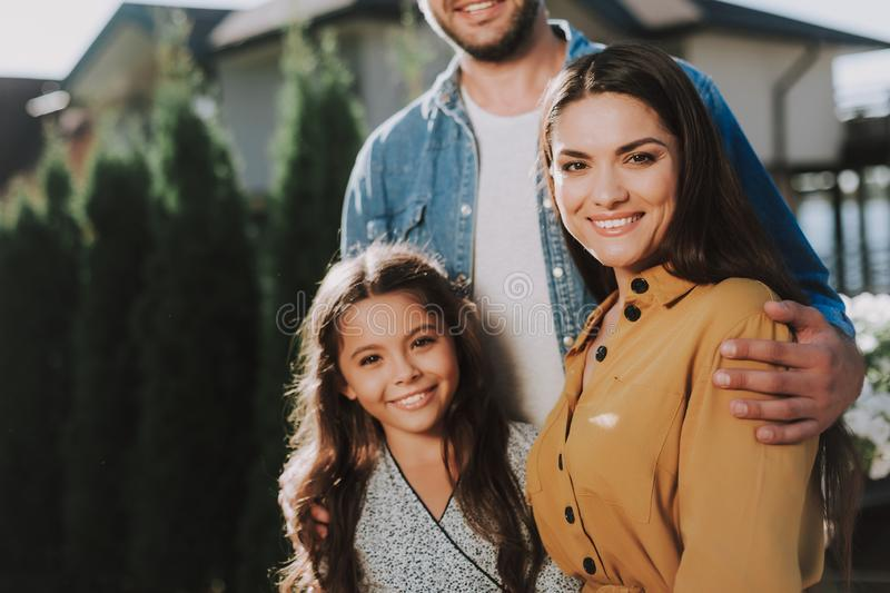 Happy parents are standing with their child stock image