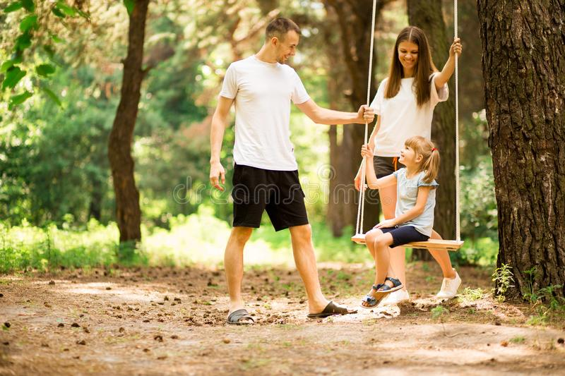 Happy parents swinging child girl at park. stock photos