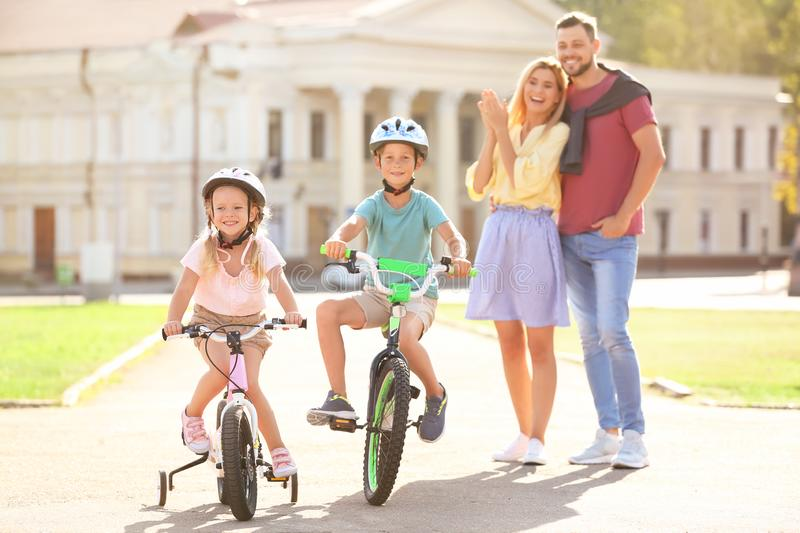 Happy parents teaching children to ride bicycles royalty free stock images