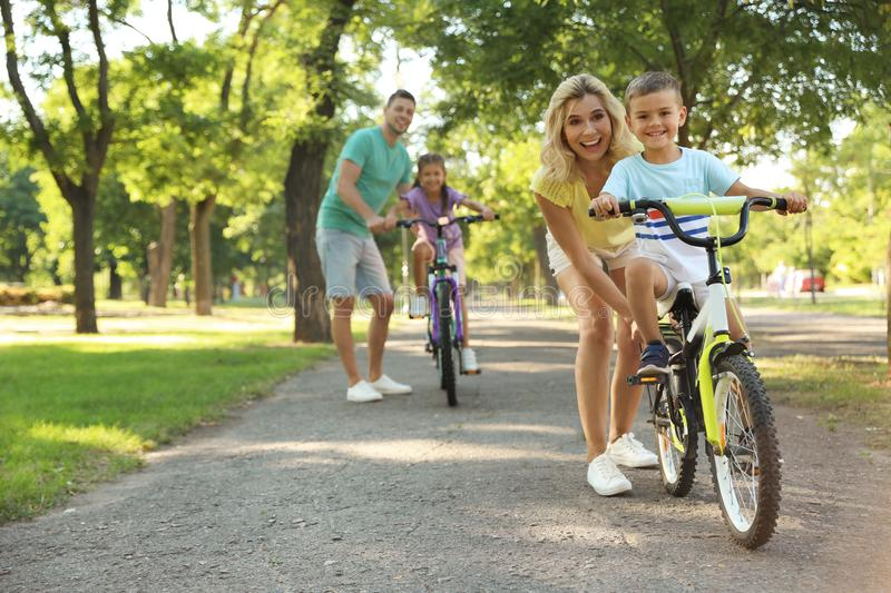 Happy parents teaching their children to ride bicycle in. Park royalty free stock photo