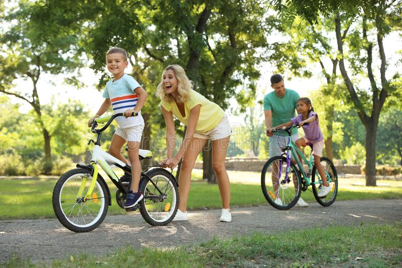 Happy parents teaching their children to ride bicycle royalty free stock image