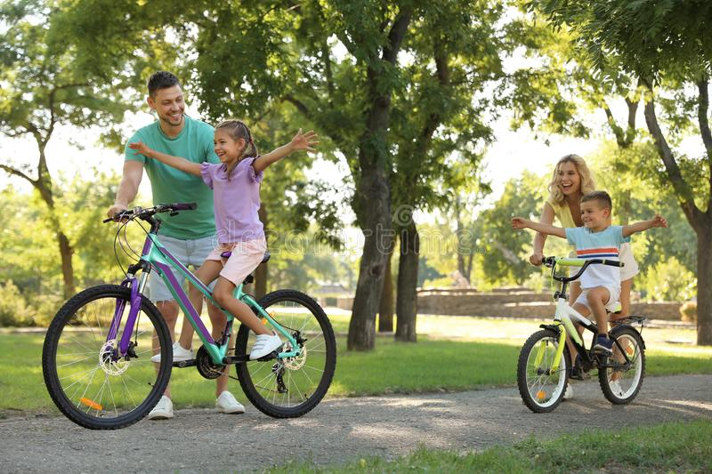 Happy parents teaching their children to ride bicycle royalty free stock photo