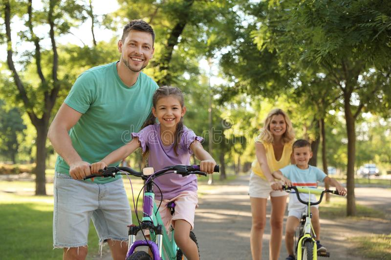 Happy parents teaching their children to ride bicycle in. Park stock photography