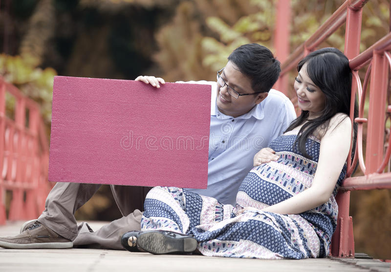 Happy parents to be holding red copyspace stock photography