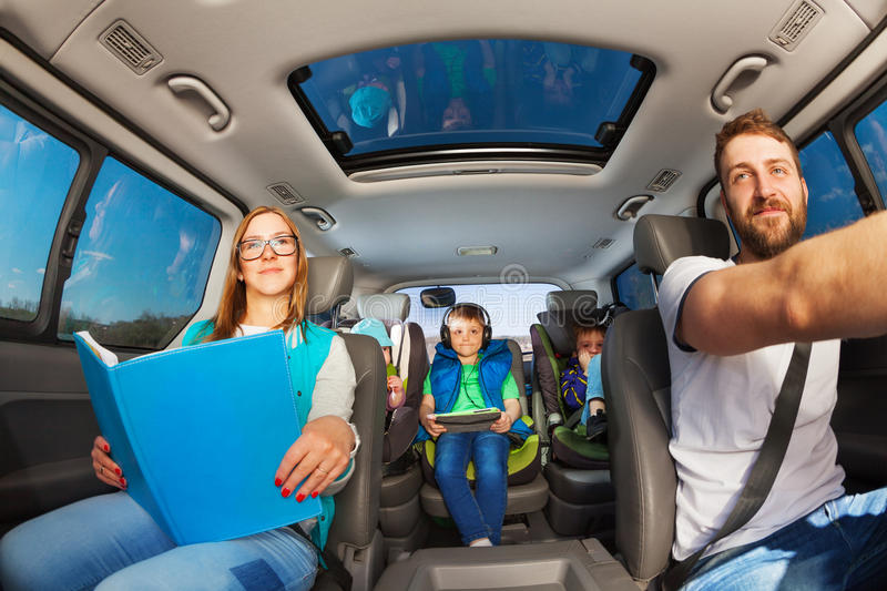 Happy parents traveling by car with kids stock photography