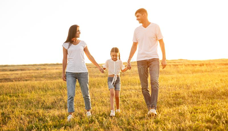 Happy parents walking with daughter in field stock image
