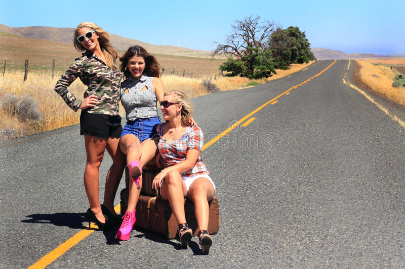 Happy Party Girls Hitch Hiking. Three happy party girls wearing short shorts and high heels are hitch hiking with their luggage on a remote desolate country road royalty free stock images