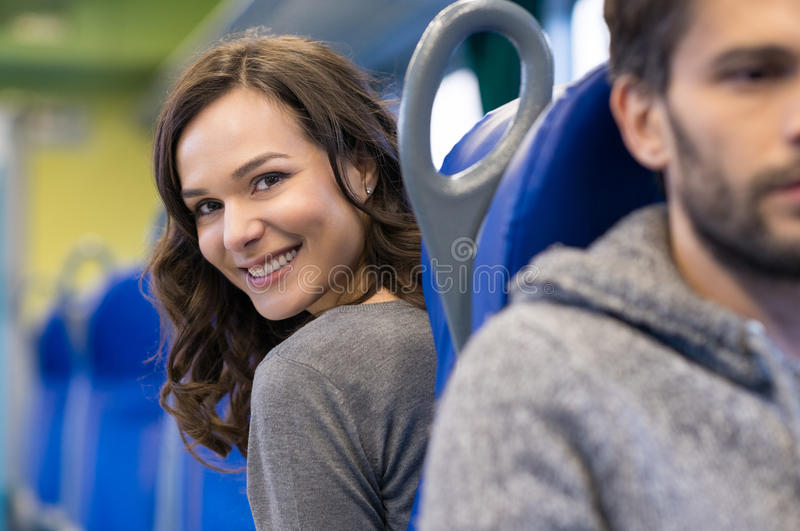 Happy passenger. Portrait of a smiling young women sitting in train. She is a brunette beautiful girl and she is looking back at camera. There are a row of blue stock photos