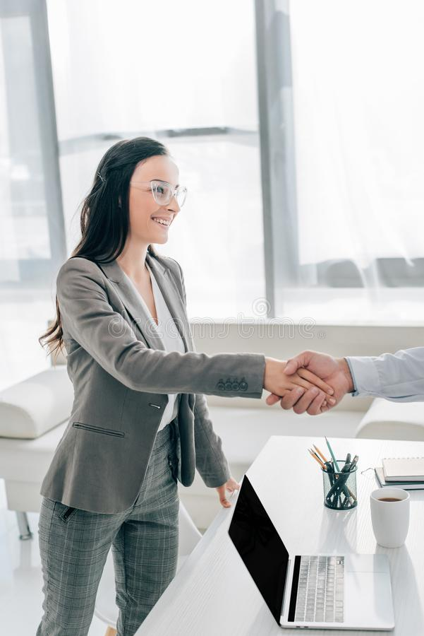 Happy patient and doctor shaking hands. In clinic royalty free stock image
