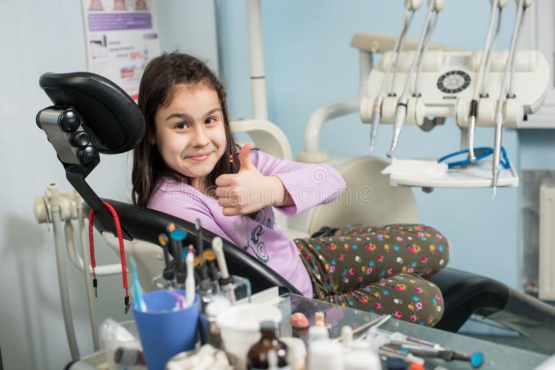 Happy patient girl showing thumbs up at dental clinic office. Medicine, stomatology and health care concept. Dental equipment royalty free stock photography