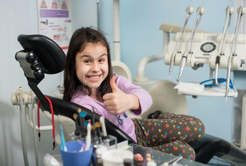 Happy patient girl showing thumbs up at dental office. Medicine, stomatology and health care concept stock photos