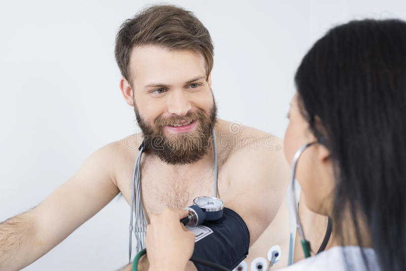 Happy Patient Looking At Doctor Checking Blood Pressure. Happy male patient looking at female doctor checking blood pressure in hospital royalty free stock image