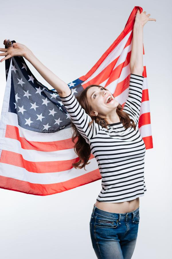 Slim cheerful woman lifting up US flag behind her back. Happy patriot. Upbeat slender young woman in a striped pullover lifting up a US flag behind her back and stock images