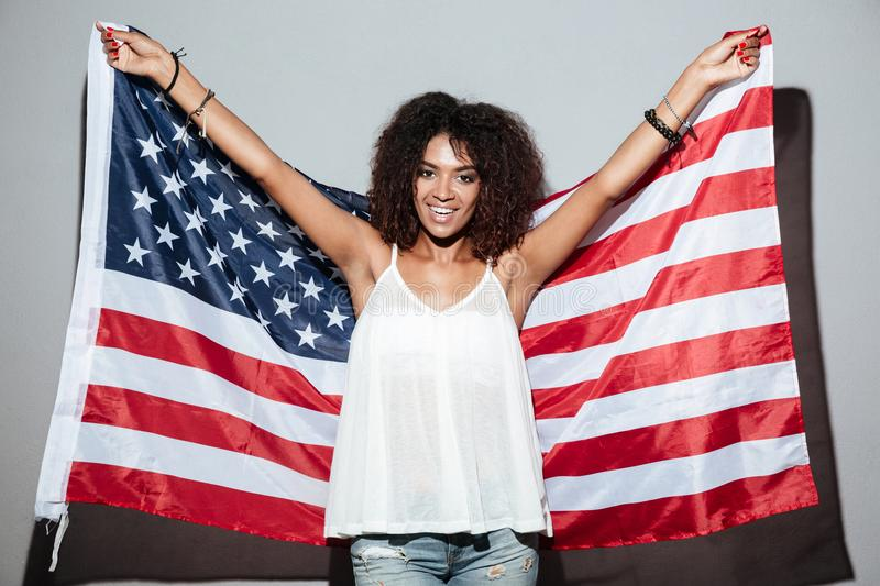 Happy patriotic african woman holding US flag. While standing over gray background stock photo