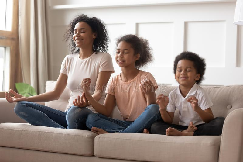 Happy black mom practice yoga with little kids. Happy peaceful young african American mom sit on couch meditate together with little children, smiling calm black royalty free stock image