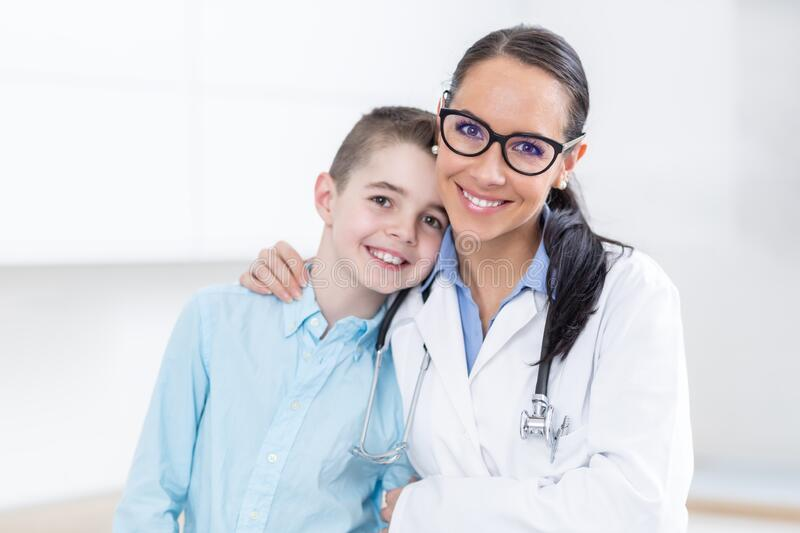 Happy pediatrician female doctor and young boy in ambulance. People and pediatry concept royalty free stock image