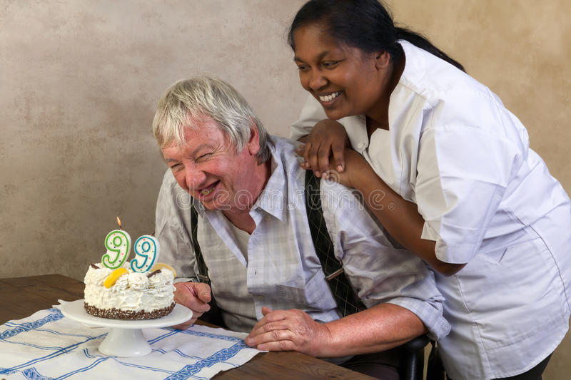 Happy pensioner with birthday cake. Elderly men in nursing home blowing out candles on his birthday cake royalty free stock photo