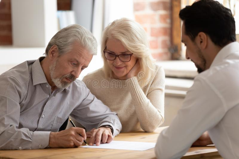 Happy mature couple close deal signing contract with realtor. Happy pensioner couple sign contract with male realtor or broker buying house or property together royalty free stock image