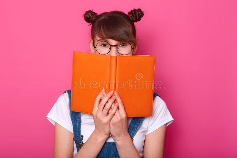 Happy pensive girl standing isolated over pink background in studio, holding orange notebook, covering half of face, looking stock photography