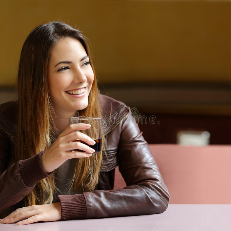 Happy pensive woman refreshing with a drink in a restaurant. And looking sideways stock images