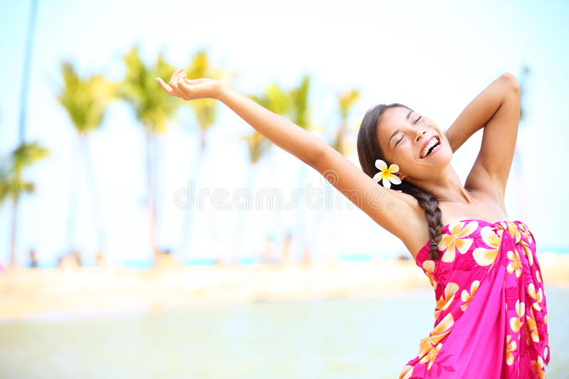 Happy people on beach travel - woman in sarong. Cheerful in happiness during summer vacation holidays on Hawaii. Multiracial Caucasian / Asian female girl stock photography