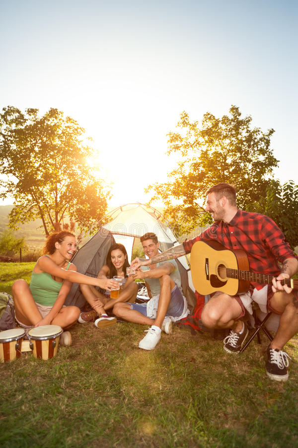Happy people on camping trip drinking beer. Fun outside of tent stock photography